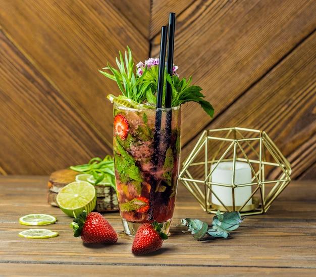 Een glas volledige tropische fruitcocktail met twee pijpen