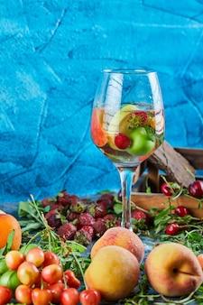 Een glas vruchtensap, doos met kersen, verse aardbeien en perziken op blauwe ondergrond