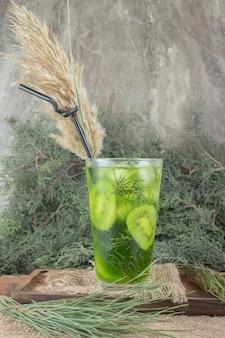 Een glas vruchtensap met kiwiplakken op houten plaat.