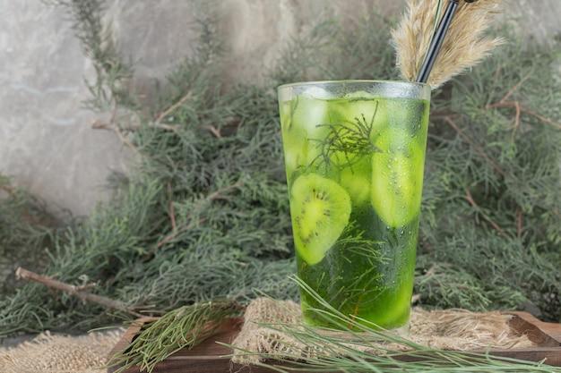 Een glas vruchtensap met kiwiplakken op houten plaat