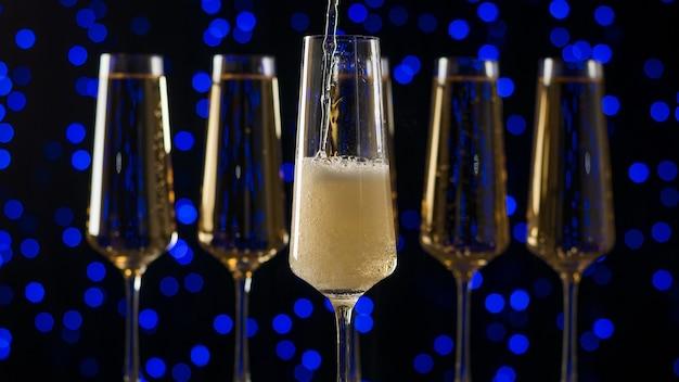 Een glas vullen met bruisende mousserende wijn op een blauwe achtergrond. een populaire alcoholische drank.