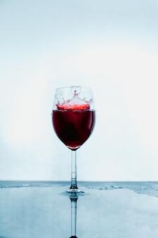 Een glas waarin rode wijn op abstracte achtergrond wordt gegoten.