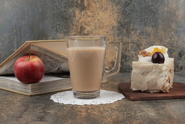 Een glas warme koffie met een rode appel en boeken op marmeren tafel.