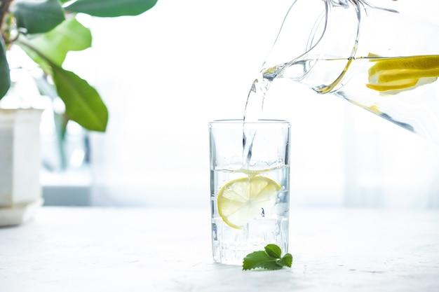 Een glas water met citroen, ijs en munt op een witte tafel gieten