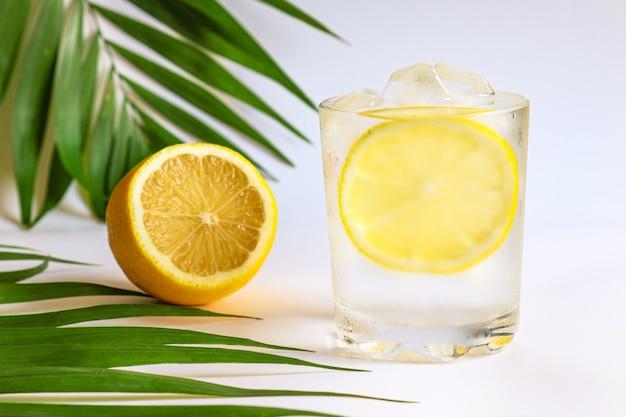 Een glas water met ijsblokjes en citroen close-up zomer verfrissende drankjes en detox concept