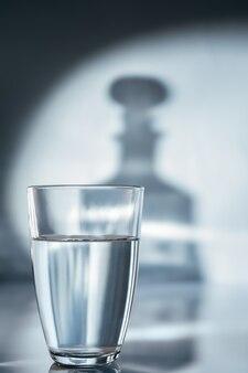 Een glas water op een blauwe achtergrond en een schaduw van een karaf
