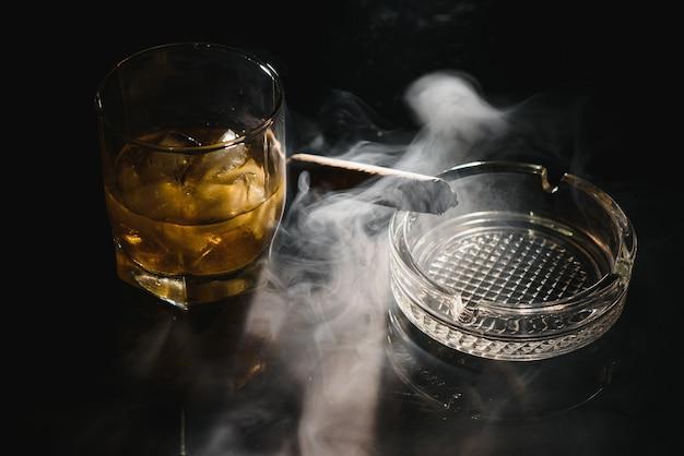 Een glas whisky of bourbon met ijsblokjes en een sigaar op een zwarte lei met rook