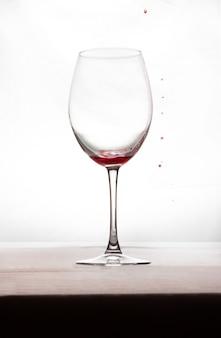 Een glas wijn met een klein beetje wijn en een paar druppels rood aan de buitenkant