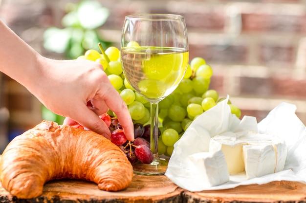 Een glas wijn met rode en groene druiven, kaas en croissant.