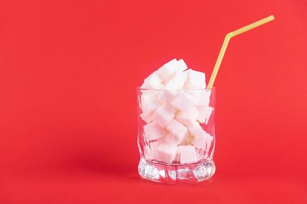 Een glas wit glas met een rietje gevuld met witte blokjes geraffineerde suiker op een rode achtergrond. ruimte kopiëren.