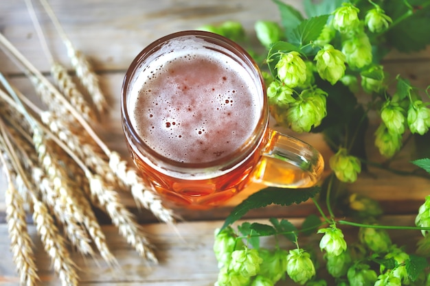 Een glas witbier op een houten oppervlak. tarwe oren en hop.