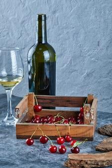 Een glas witte wijn, een fles en een houten kist met kersen op blauwe ondergrond