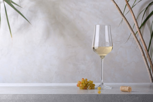 Een glas witte wijn, een kurk en een tros druiven op een stenen tafel. lichte achtergrond.