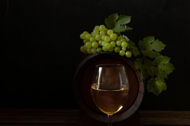 Een glas witte wijn, een tros druiven met bladeren en een wijnvat