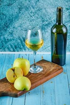 Een glas witte wijn en een fles met appelschijfjes op blauwe muur.