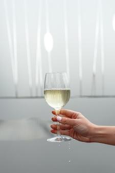 Een glas witte wijn in de hand van een vrouw