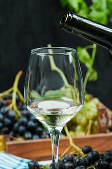 Een glas witte wijn met een tros rode druiven.