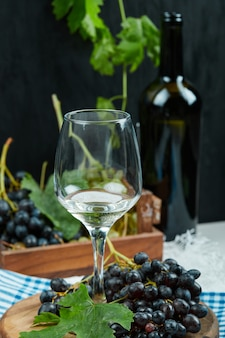 Een glas witte wijn met fruit apart.