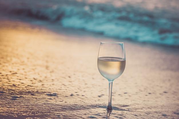 Een glas witte wijn op het strand bij zonsondergang.