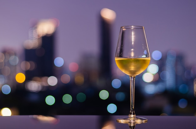 Een glas witte wijn op tafel van bar op het dak met kleurrijke bokeh stadslichten