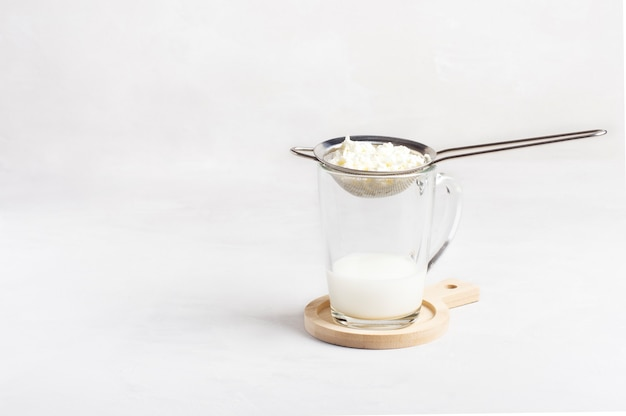 Een glas zelfgemaakte kefir met kefirkorrels staat op een witte achtergrond