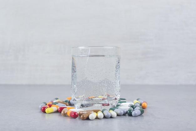 Een glas zuiver water met kleurrijke pillen op grijze achtergrond.