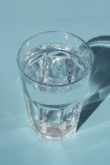 Een glas zuiver water onder zonlicht met diepe stijlvolle schaduwen op blauwe copyspace