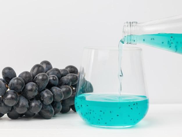 Een glasglas vullen met een exotische cocktail op een van blauwe druiven. een exotisch verfrissend drankje.