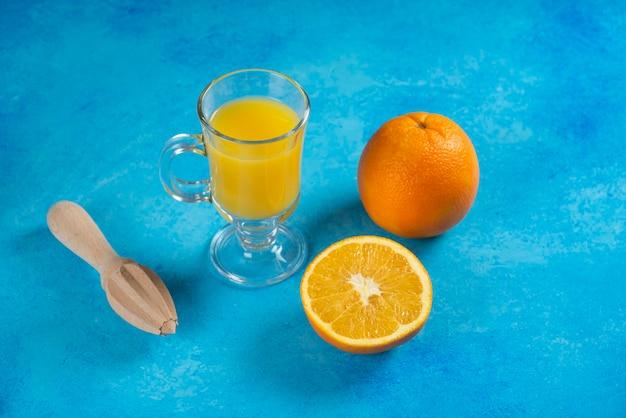 Een glaskoppen sinaasappelsap op blauw.