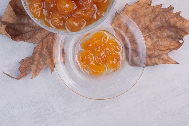 Een glasplaat van jam op wit oppervlak