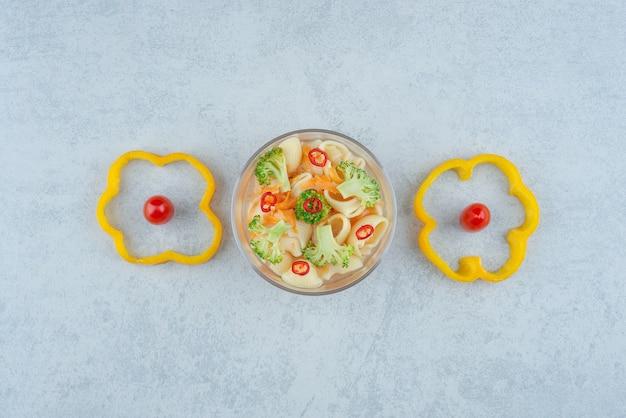 Een glasplaat van macaroni en broccoli op witte achtergrond. hoge kwaliteit foto