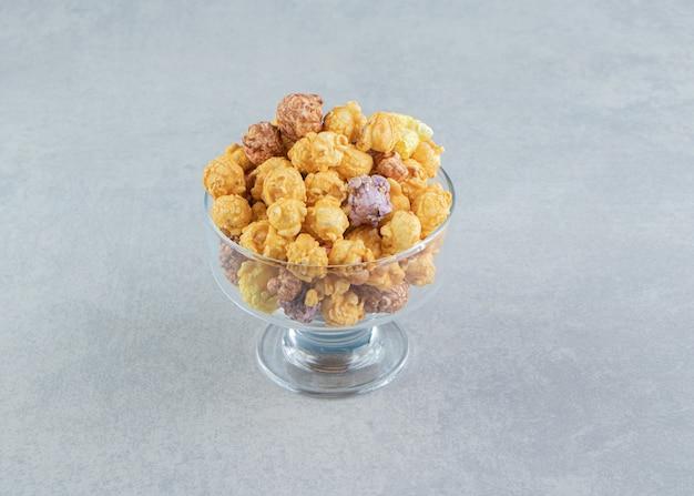 Een glasplaat vol popcorn met karamel.