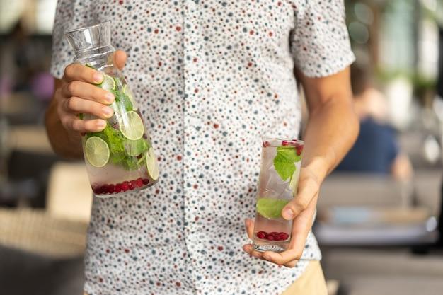 Een glazen beker en een karaf met een koud verfrissend zomers vruchtensap van munt en cranberry limoenlimonade in de handen van een jonge man in een shirt met korte mouwen.