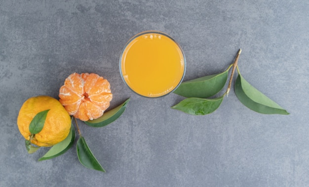 Een glazen beker mandarijnsap met bladeren