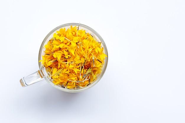 Een glazen beker met bloemblaadjes van goudsbloem. bloem kruidenthee concept.
