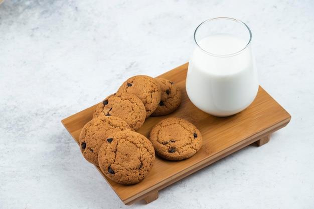 Een glazen beker met chocoladekoekjes op een houten bureau.