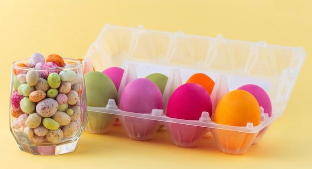 Een glazen beker met gekleurde snoepjes en een bakje met heldere paaseieren.