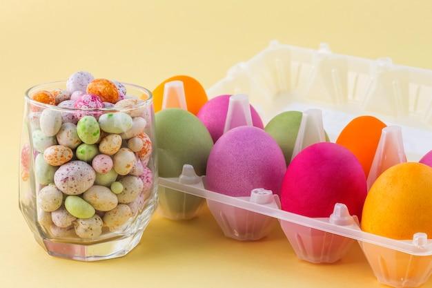 Een glazen beker met gekleurde snoepjes en een container met heldere paaseieren close-up.
