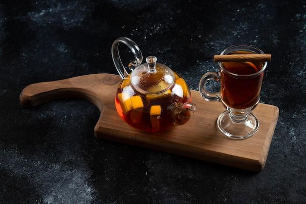 Een glazen beker met hete thee en kaneelstokjes.