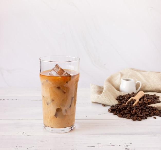 Een glazen beker met koude koffie en ijs, koffiebonen