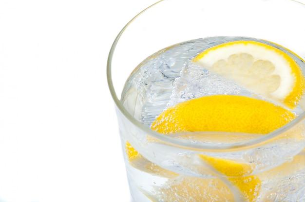 Een glazen beker met kristalhelder water, citroen en ijsblokjes.