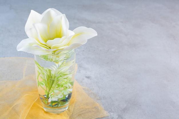 Een glazen beker met mooie witte bloem op geel tafelkleed.