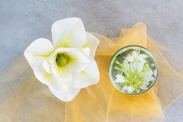 Een glazen beker met mooie witte bloem op geel tafelkleed