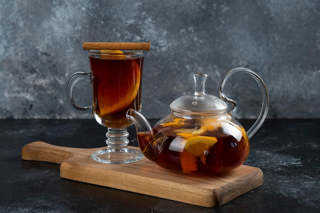 Een glazen beker met thee en kaneelstokjes.