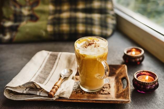 Een glazen beker pompoenkruid latte naast een raam