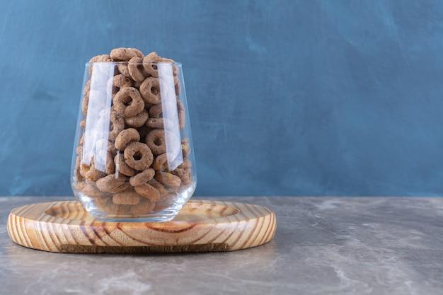 Een glazen beker vol chocoladegranen ringen op een houten bord.