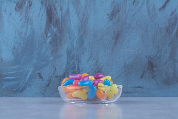 Een glazen beker vol kleurrijke bonen snoepjes op grijze tafel.
