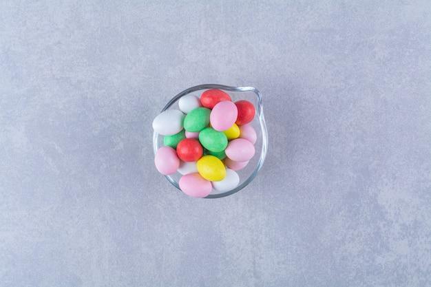 Een glazen beker vol kleurrijke bonensnoepjes.