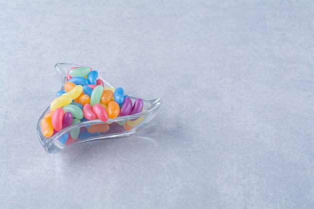 Een glazen beker vol kleurrijke bonensnoepjes