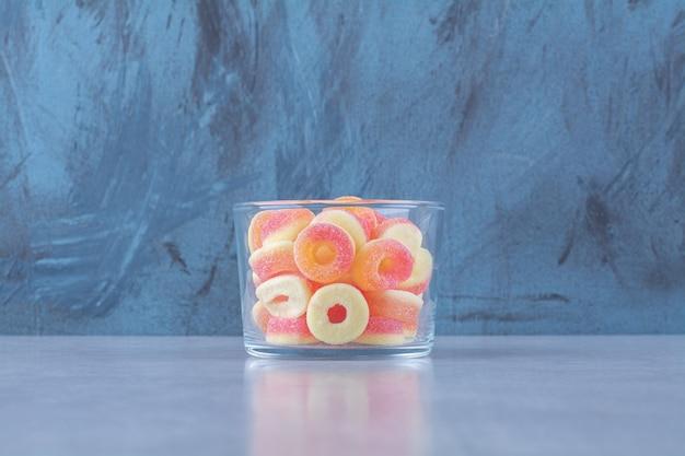 Een glazen beker vol kleurrijke fruitige suikermarmelades.
